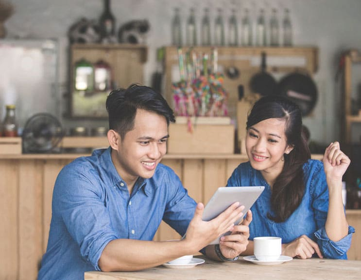 one malay guy holding iPad with a woman